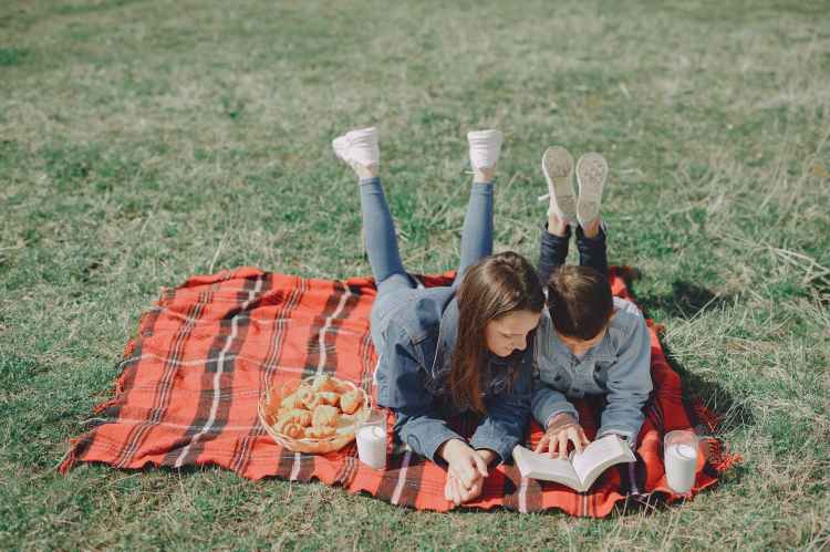 casual siblings resting on picnic in park