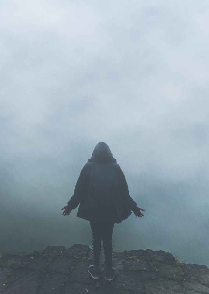 back view of person standing in fog